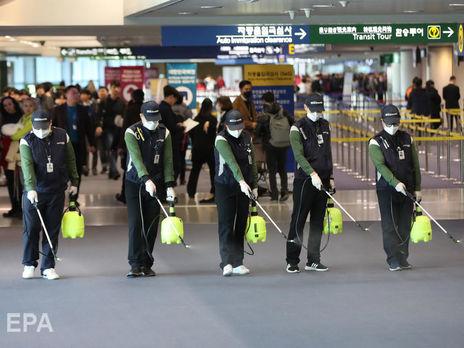 """21 січня. Співробітники карантинної служби в межах боротьби з поширенням коронавірусу розпорошують дезінфектант в аеропорту """"Інчхон"""", Південна Корея"""