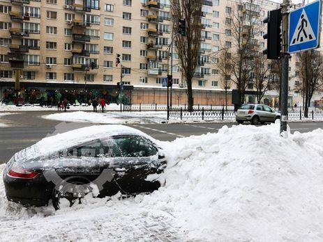 В Киеве коммунальщики засыпали снегом припаркованный Porshe