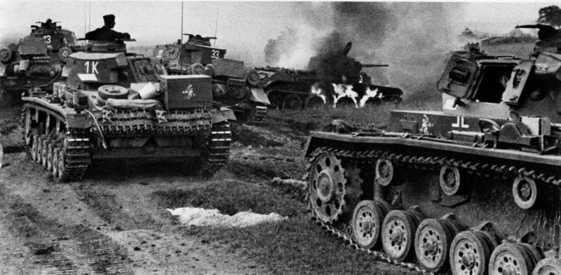 Немецкие танки Pz.III и Pz.IV проезжают мимо горящего советского танка БТ-7. Фото: waralbum.ru
