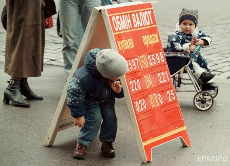 A child plays hide-and-seek under a board carrying exchange rates in downtown Kiev 21 October 1998. Фото: ЕРА