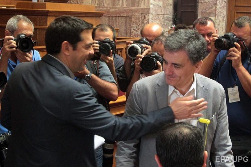Премьер-министр Греции Алексис Ципрас приветствует нового министра финансов Евклида Цакалотоса в парламенте Греции 10 июля. Предыдущий глава Минфина страны
